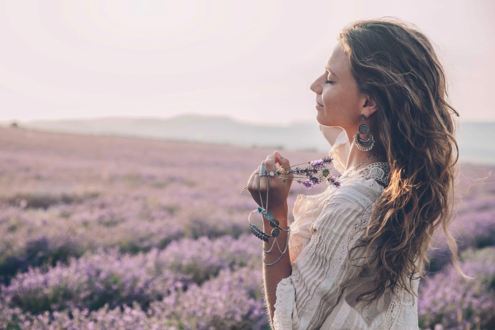 Frau steht in einer Blumenwiese und fühlt sich gut