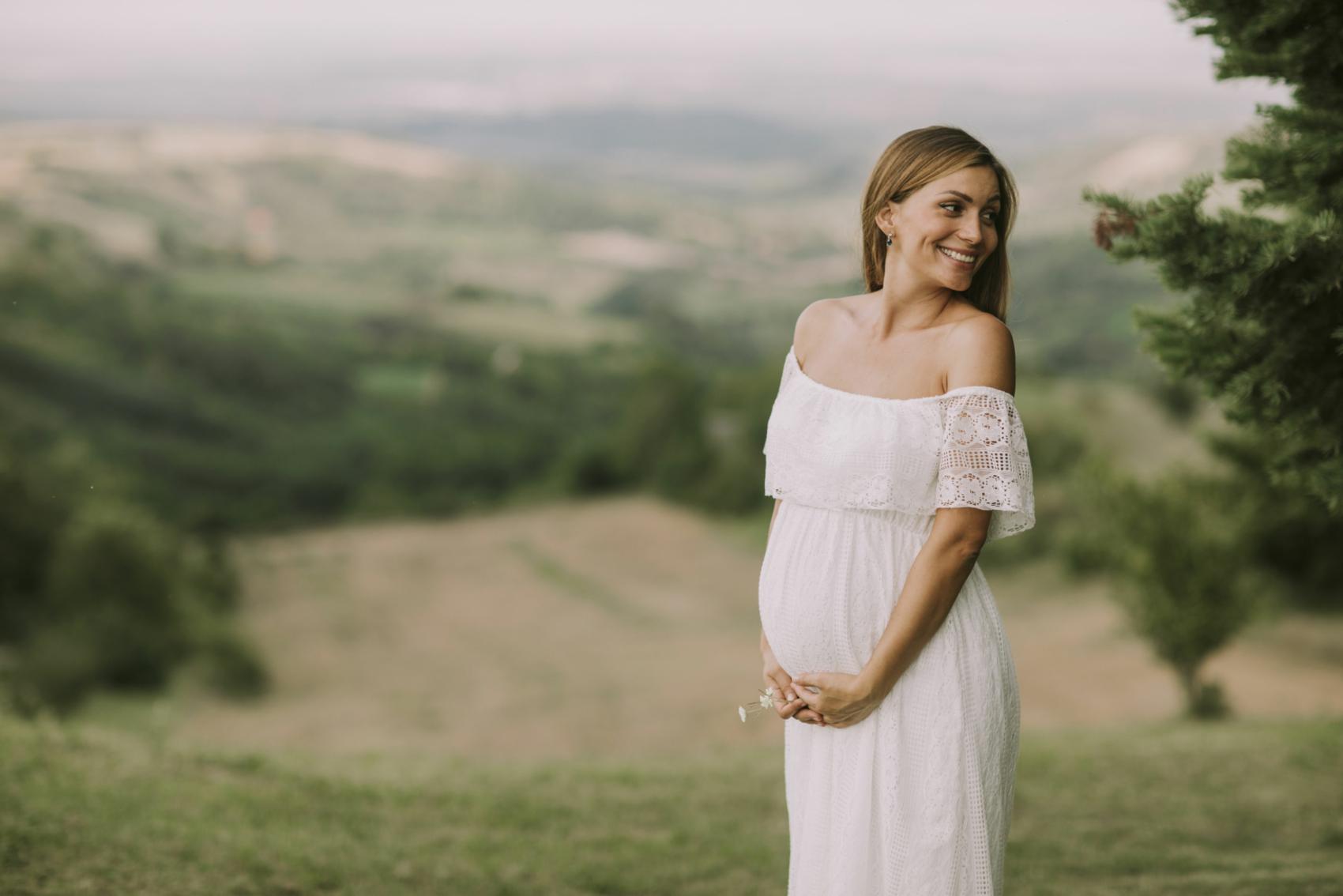 Schwangere Frau steht in der Natur in weißem Kleid